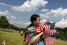 Girl Scout Megan Lontoc, 10, has her arms full of Flags as scouts placed thousands of flags on veteran's graves at Brig. Gen. William C. Doyle Veterans Memorial Cemetery in honor of Memorial Day, Friday, May 27, 2016, in Wrightstown N.J. (AP Photo/Mel Evans)