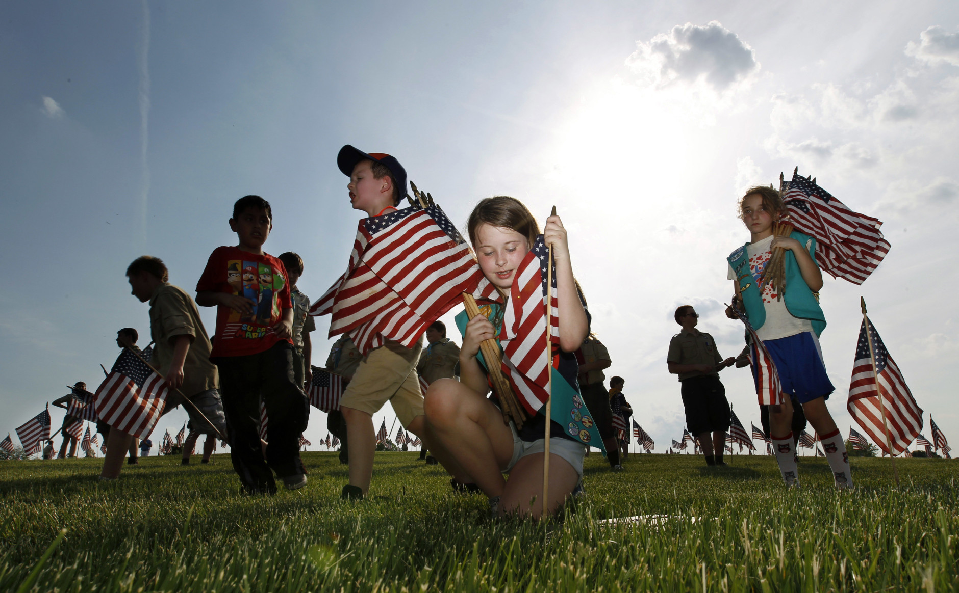 Throngs of scouts rush to place thousands of flags on veteran's graves at Brig. Gen. William C. Doyle Veterans Memorial Cemetery in honor of Memorial Day, Friday, May 27, 2016, in Wrightstown N.J. (AP Photo/Mel Evans)