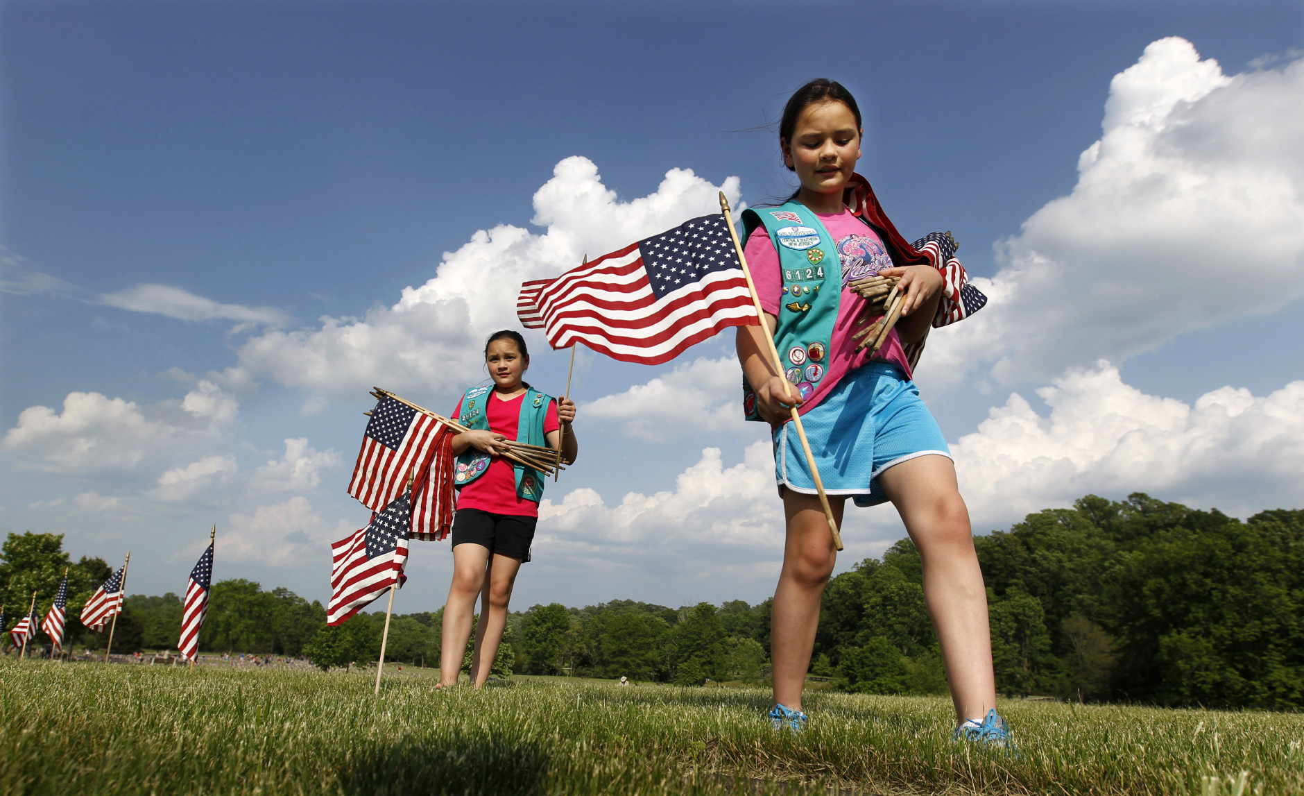 Twin Girl Scouts Sarah and Megan Lontoc, 10, place flags as the scouts placed thousands of flags on veteran's graves at Brig. Gen. William C. Doyle Veterans Memorial Cemetery in honor of Memorial Day, Friday, May 27, 2016, in Wrightstown N.J. (AP Photo/Mel Evans)