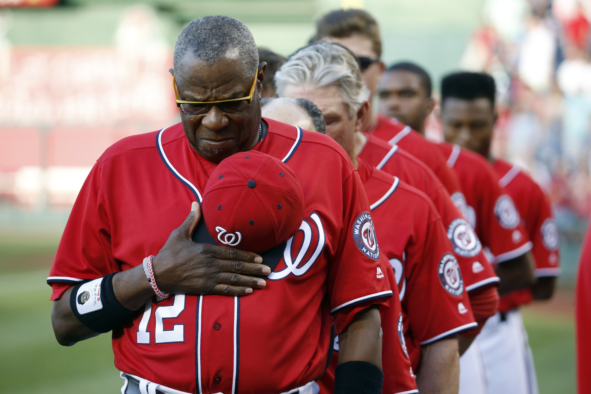 Washington Nationals manager Dusty Baker (12) and the other members of his team observe a moment of silence for Memorial Day, before a baseball game against the St. Louis Cardinals at Nationals Park, Saturday, May 28, 2016, in Washington. (AP Photo/Alex Brandon)