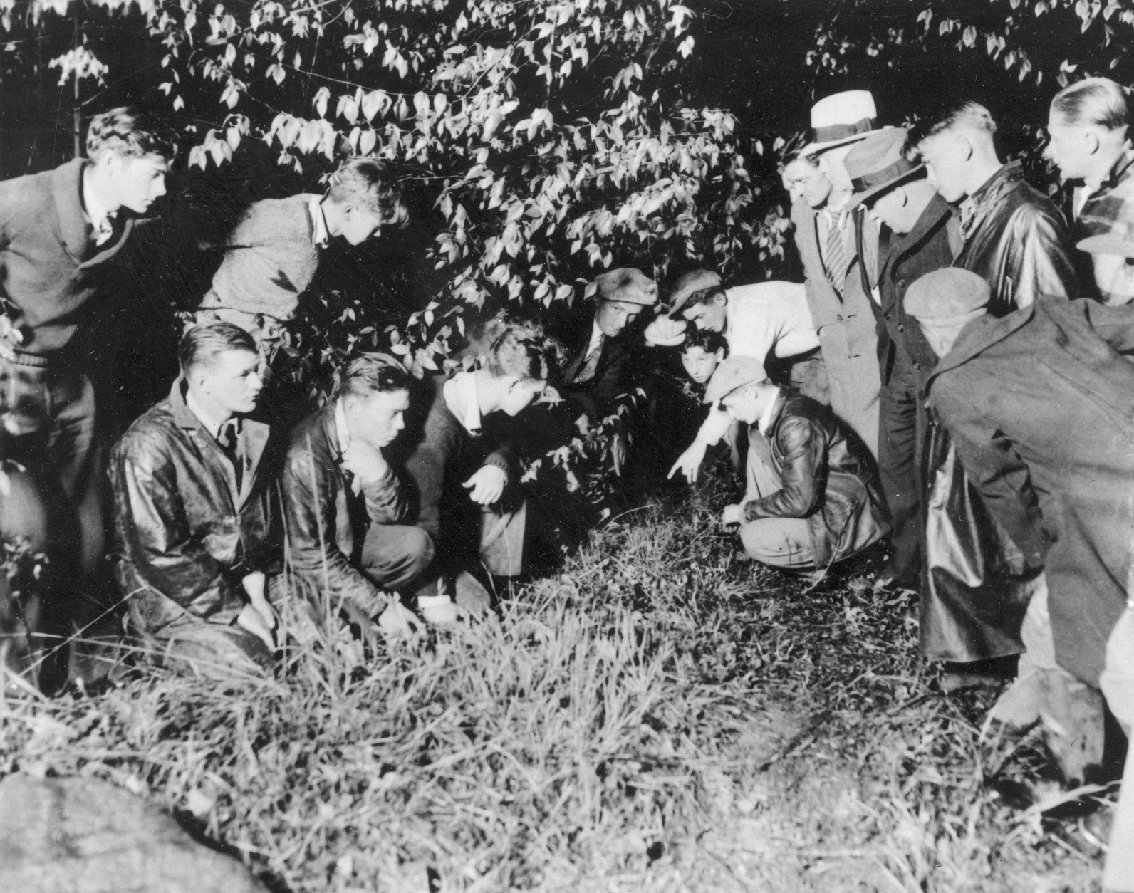 Newsmen and spectators are watching as a young man points to the spot where the body of 19-month-old baby Charles A. Lindbergh Jr., was found in a shallow grave, near Mount Rose, N.J., on May 12, 1932. The infant son of world-famed aviator Charles Lindbergh was kidnapped on March 1, 1932, and found dead today, only four-and-a-half miles away from the Lindbergh estate.  (AP Photo)