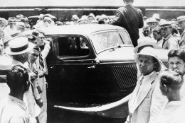 People crowd around the abandoned bullet-riddled 1934 Ford automobile in which Bonnie Parker and Clyde Barrows were killed by federal agents in Arcadia, La., May 23, 1934.  (AP Photo)