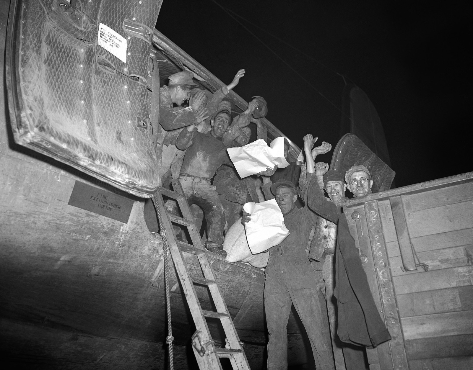A cargo handling crew at Tempelhof airfield in Berlin pause in their task of unloading a Skymaster plane of the Berlin airlift, May 5, 1949 to raise a cheer over the news of the lifting of the German capital, scheduled for May 12. The airlift, however, is planned to be continued despite the proposed end of the Berlin siege. (AP Photo)