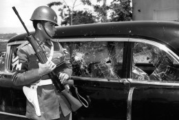 An armed guard stands by the car in which Vice President Richard Nixon rode through jeering, rock-throwing mobs May 13, 1958, in Caracas, Venezuela.  (AP Photo)