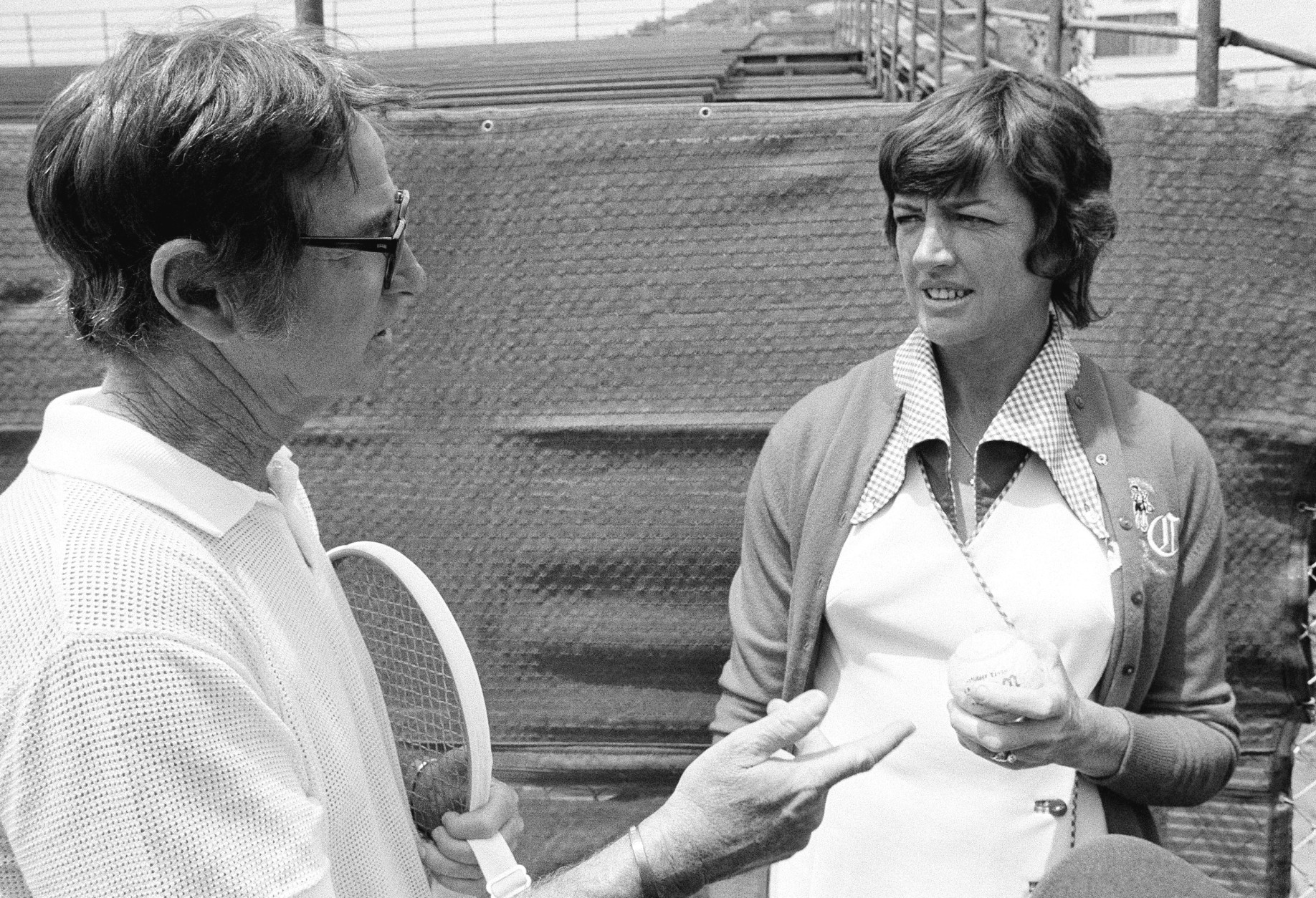 Bobby Riggs, former Wimbledon tennis star, talks with Margaret Court about heavy duty tennis ball she has selected for their $10,000 challenge match in Ramona, Calif., May 12, 1973. She won a coin toss on Thursday and selected the heavier ball. Riggs attempted to talk Margaret into using a livelier ball in their best-of-three set match. Margaret stuck with her original decision. (AP Photo/Wally Fong)