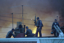 Armed Philadelphia police officers man a rooftop as the sky is illuminated by the flames from a neighborhood in West Philadelphia, Pa., that burned after police dropped a bomb on a building occupied by members of anarchist group MOVE, May 13, 1985.  (AP Photo/George Widman)