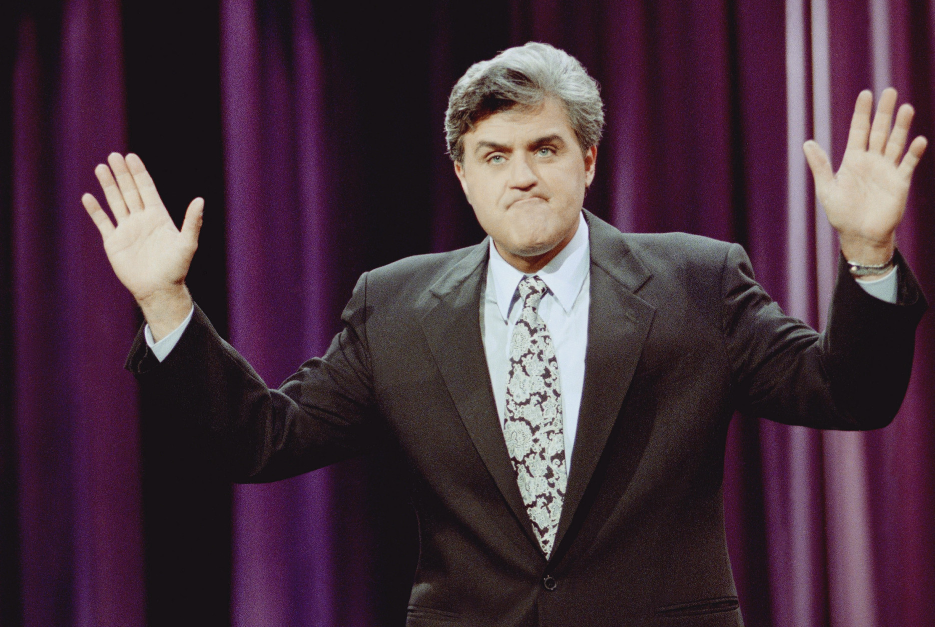 "Jay Leno gestures during the opening monologue at the inauguration of ""The Tonight Show with Jay Leno"" which was broadcast live on the east coast from NBC Studios in Burbank, Calif., May 25, 1992. The show features a new band with jazz musician Branford Marsalis as musical director. Leno's first guests were comedian Billy Crystal and singer Shanice. (AP Photo/Craig Fujii)"