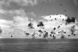 The U.S. aircraft carrier Yorktown, left, and other fighting ships of the U.S. task force in the Pacific, throw up an umbrella of anti-aircraft fire to fight off a squadron of Japanese torpedo planes attacking the carrier during the Battle of Midway, June 4, 1942. A small column of smoke, far left, rises from a Japanese plane that was shot down near the carrier. (AP Photo)