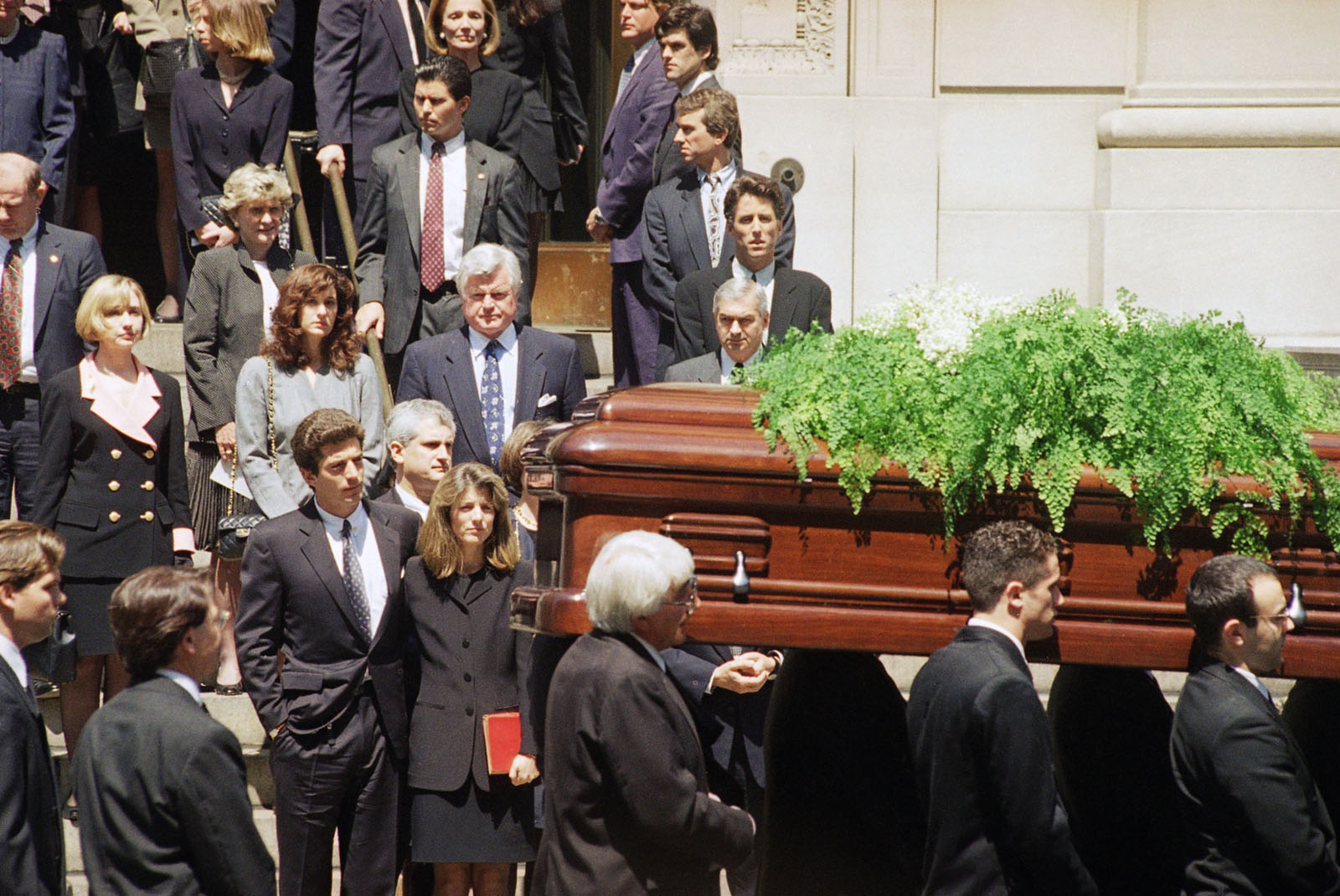 The casket bearing the remains of Jacqueline Kennedy Onassis is carried out of St. Ignatius Loyola Roman Catholic Church in New York following a funeral mass  Monday, May 23, 1994. Following immediately behind the pallbearers are John F. Kennedy Jr., with an arm around his sister, Caroline Kennedy Schlossberg; Caroline's husband, Edwin Schlossberg, is visible between them. Hillary Rodham Clinton, left; Sen. Edward M. Kennedy (D-Mass.) and his wife, Victoria Reggie, center; and at right, third from bottom, Robert F. Kennedy Jr. (AP Photo/Elise Amendola)