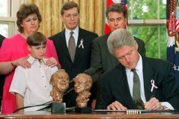 """President Clinton signs the """"Megan's Law,"""" named after the late Megan Kanka of Hamilton Township, N.J., Friday May 17, 1996 in the Oval Office of the White House. Looking on from left are, Megan's mother Maureen, brother Jeremy, 7, Rep. Dick Zimmer, R-N.J., and John Walsh, host of the """"America's Most Wanted"""" television show. (AP Photo/Denis Paquin)"""