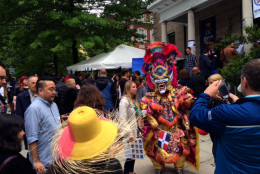 Visitors pose with a dancer in costume outside the Embassy of the Dominican Republic during the Embassy Tour in D.C. on Saturday, May 7, 2016. (WTOP/Dennis Foley)