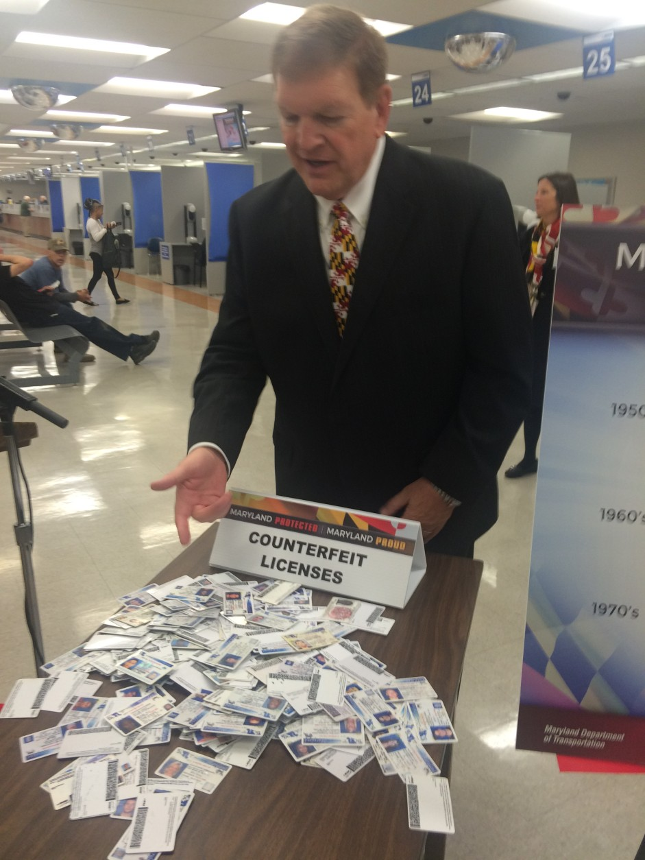 Maryland Transportation Secretary Pete Rahn with a pile of fake driver's licenses confiscated by a Howard County Police Officer. (WTOP/Dick Uliano)