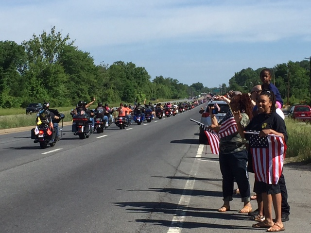 Onlookers along Route 10 in Maryland wave flags at passing motorcycles on their way to Rolling Thunder on Sunday, May 29. (Darci Marchese/WTOP)