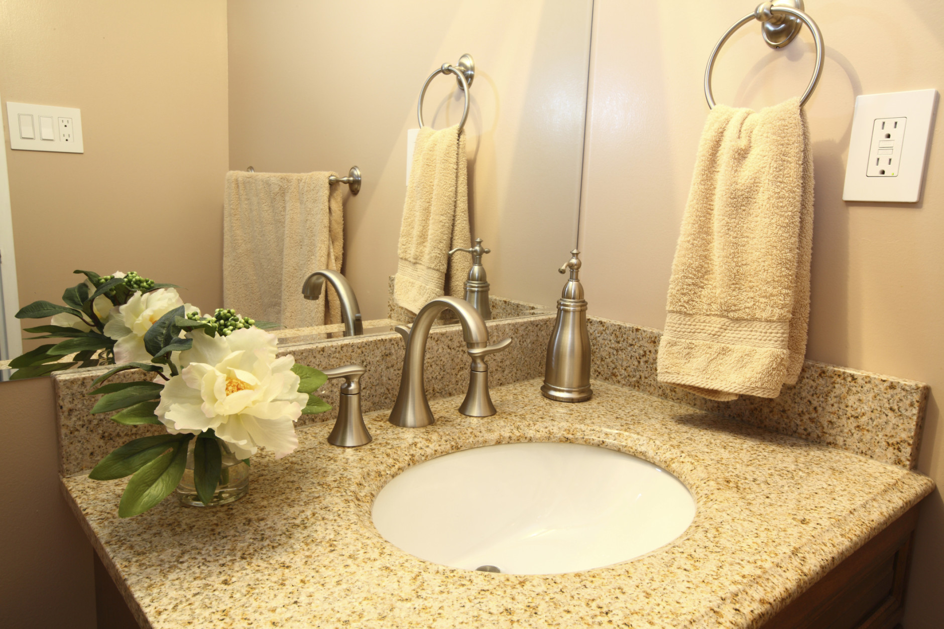 Modern bathroom vanity with beige granite top and faucets (Getty Images/iStockphoto/bukharova)
