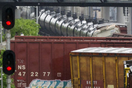 Officials look down from a Metro pedestrian bridge at several overturned train cars after a CSX freight train derailed in Washington on Sunday, May 1, 2016. (AP Photo/Cliff Owen)