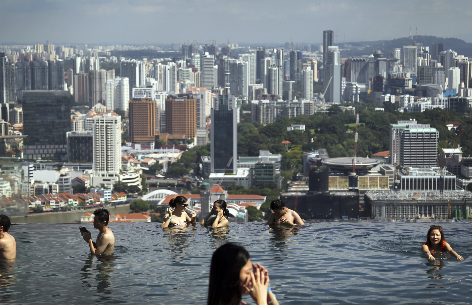 FILE - In this May 13, 2013 file photo, swimmers soak in a swimming pool overlooking the financial skyline in Singapore. Travelers often use Singapore as a quick stopover on long flights but there are plenty of attractions here to justify a visit of several days. (AP Photo/Wong Maye-E, File)