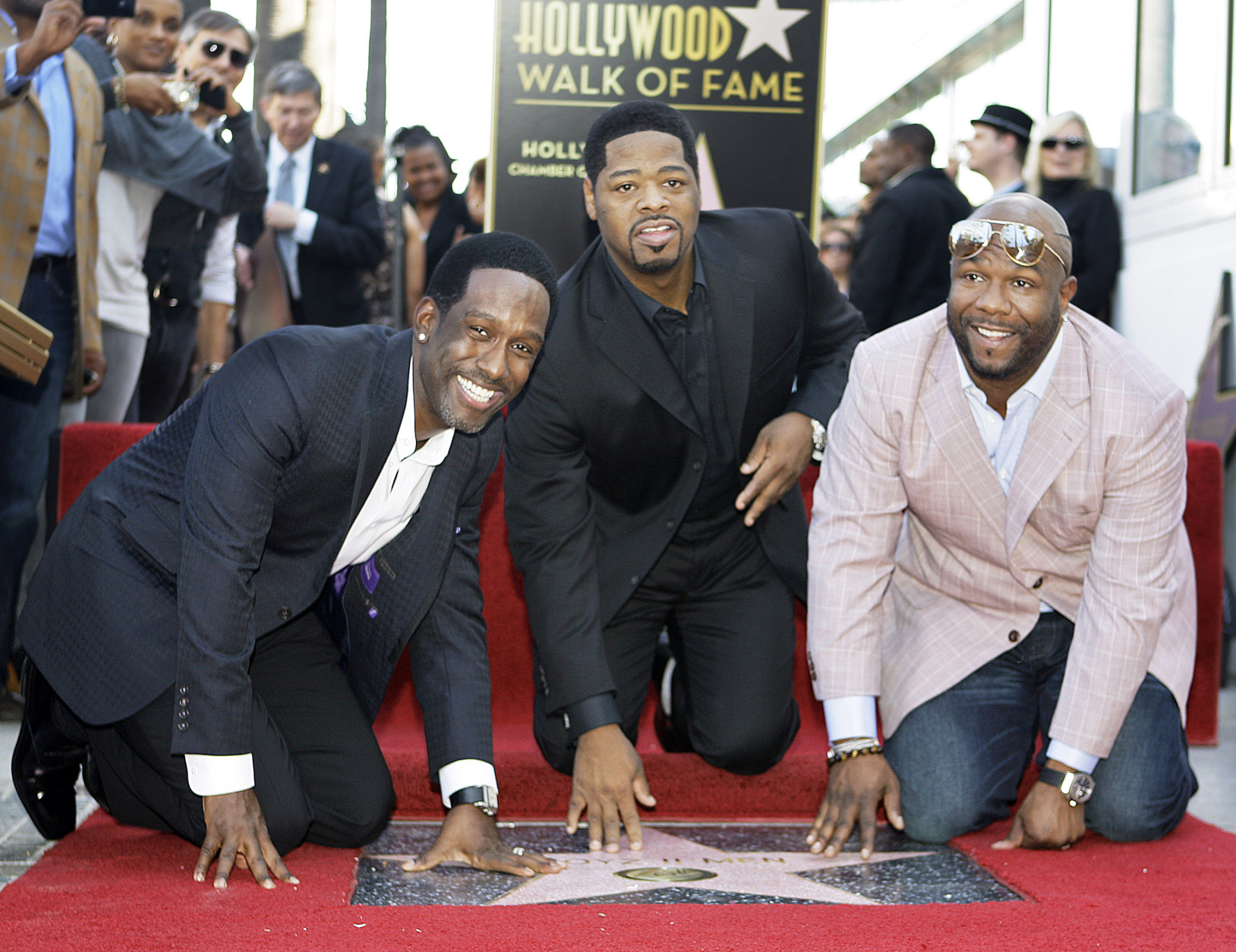 The R&B group Boyz II Men, from left, Shawn Stockman, Nathan Morris and Wanya Morris, touch their new star on the Hollywood Walk of Fame at dedication ceremonies in Los Angeles on Thursday, Jan. 5, 2012. (AP Photo/Reed Saxon)