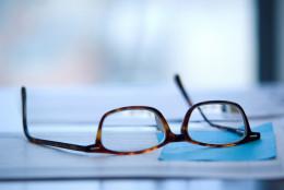 Reading glasses laid on desktop.