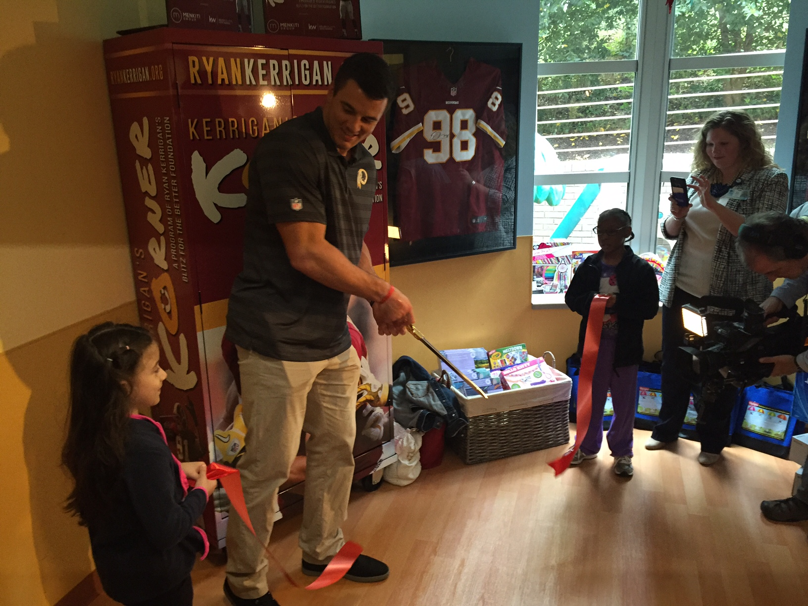 As he cut the ribbon on the opening of his third Kerrigan's Korner, the Redskins player said days like this are rewarding to him. (WTOP/Megan Cloherty)