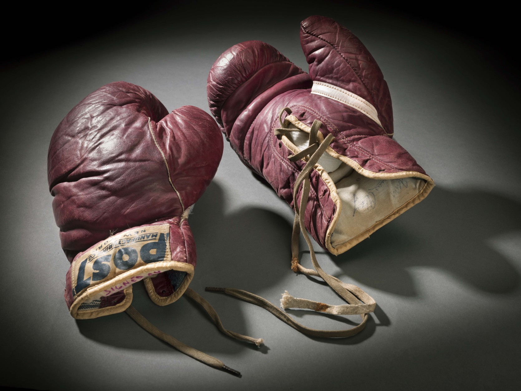 Cassius Clay (Muhammad Ali) Training Gloves, Post Manufacturing Co., circa 1960; leather, cotton, L. 10 x W. 5 1/2 x D. 4 in.  Studio photograph on gray background by NASM Photographer Eric Long, February 26, 2013, at 3400 Pennsy Drive, Washington, DC.  Credit: Collection of the Smithsonian National Museum of African American History and Culture (2012.173.3ab)