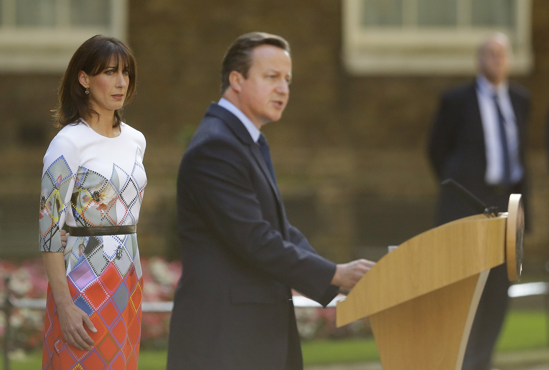 Britain's Prime Minister David Cameron speaks outside 10 Downing Street, London as his wife Samantha looks on Friday, June 24, 2016. Cameron says he will resign by the time of the party conference in the fall after  Britain voted to leave the European Union after a bitterly divisive referendum campaign, according to tallies of official results Friday. (AP Photo/Matt Dunham)