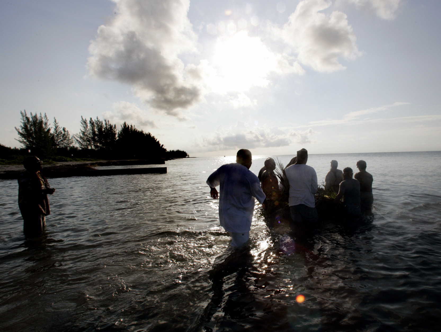 "A group of men wade into the ocean as they push a small raft loaded with offerings to their ancestors out to sea Sunday, June 19, 2005 on Virginia Key, Miami's former ""black only"" beach. The ceremony is part of the Juneteenth celebration, an unofficial black holiday that marks the day on June 19, 1865 when slaves in Texas learned that Abraham Lincoln had signed the Emancipation Proclamation two years earlier. (AP Photo/Wilfredo Lee)"
