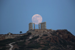 The full moon rises behind the columns of the ancient marble Temple of Poseidon at Cape Sounion, southeast of Athens, on the eve of the summer solstice on June 20, 2016.  The temple located on a promontory at Cape Sounion,  about 70 Km (45 miles) south-southeast of Athens, built 444 BC, and dedicated to Poseidon, god of the sea. (AP Photo/Petros Giannakouris)