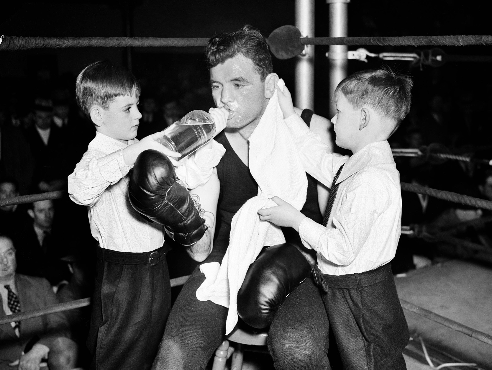 James J. Braddock, heavyweight champion, is working out at Stillmans Gym and was helped  by his two sons Jay, left, and Howard, Jan. 27, 1937 in New York. (AP Photo)