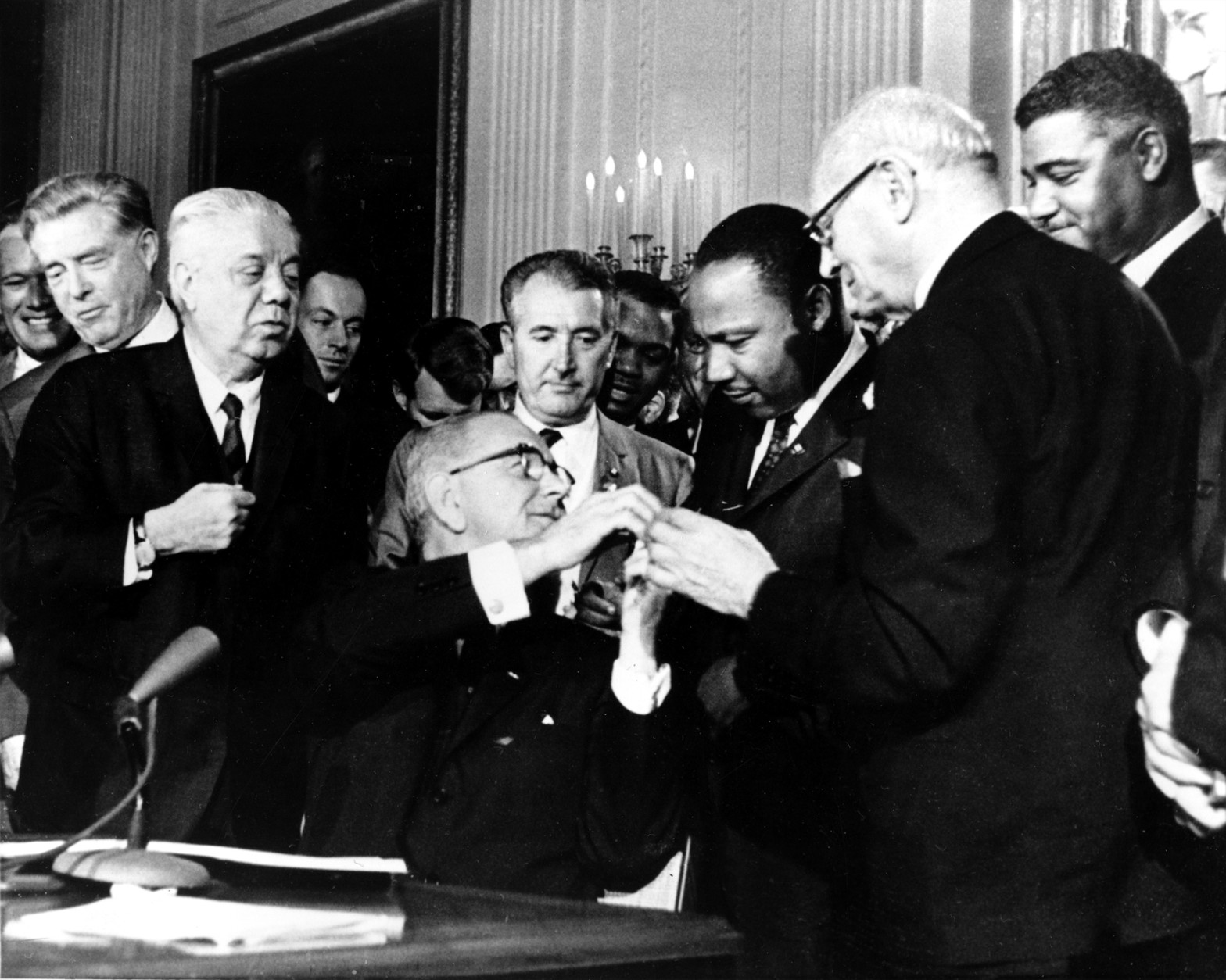 U.S. President Lyndon B. Johnson reaches to shake hands with Dr. Martin Luther King Jr. after presenting the civil rights leader with one of the 72 pens used to sign the Civil Rights Act of 1964 in Washington, D.C., on July 2, 1964.  Surrounding the president, from left, are, Rep. Roland Libonati, D-Ill., Rep. Peter Rodino, D-N.J., Rev. King, Emanuel Celler, D-N.Y., and behind Celler is Whitney Young, executive director of the National Urban League.  (AP Photo)