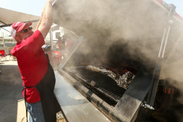 """IMAGE DISTRIBUTED FOR KINGSFORD - Rescue Smokers team captain Robby Royal prepares his """"Pick Your Pork"""" entry during the Kingsford Invitational on Saturday, May 2, 2015 at Hudson River Park's Pier 26, New York. (Photo by Matt Peyton/Invision for Kingsford/AP Images)"""