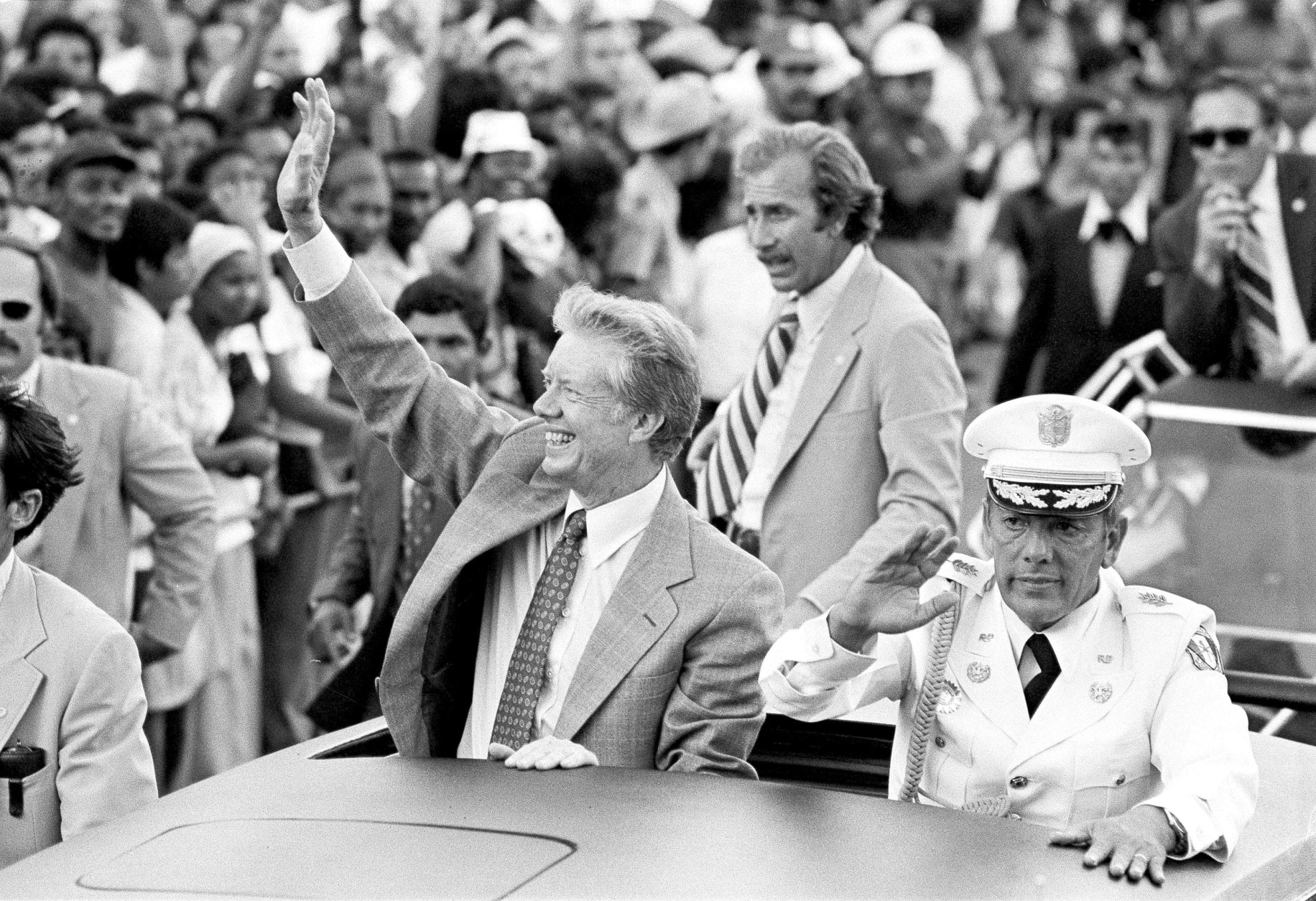 President Jimmy Carter and General Omar Torrijos wave from an open car during a motorcade Friday in Panama City, Panama, June 16, 1978. (AP Photo)