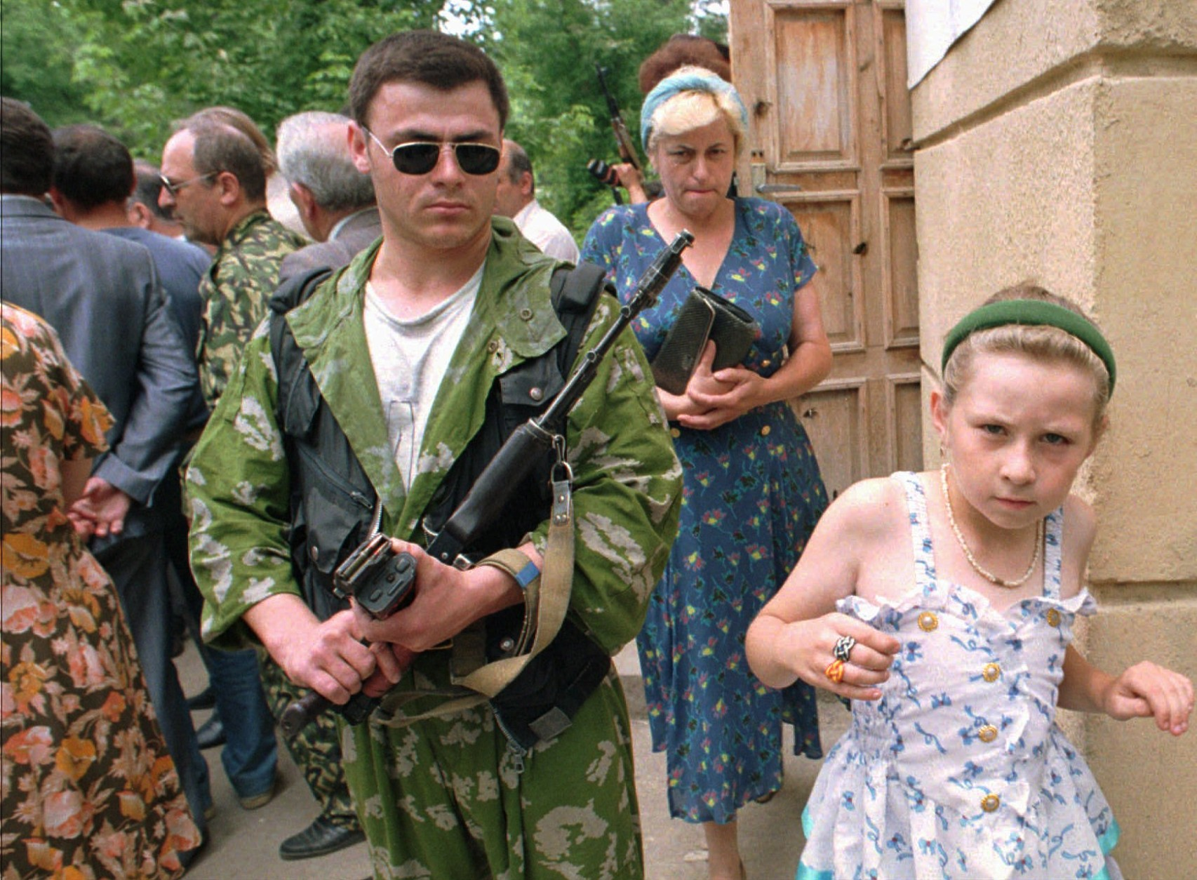 People leave a polling  station in Grozny, capital of war torn Chechnya, under the watchful eye of a Russian soldier, after voting in local and Russian presidential elections, Sunday June 16 1996. Polsters make the presidential election a very close call. (AP Photo/Shakh Aivazov).