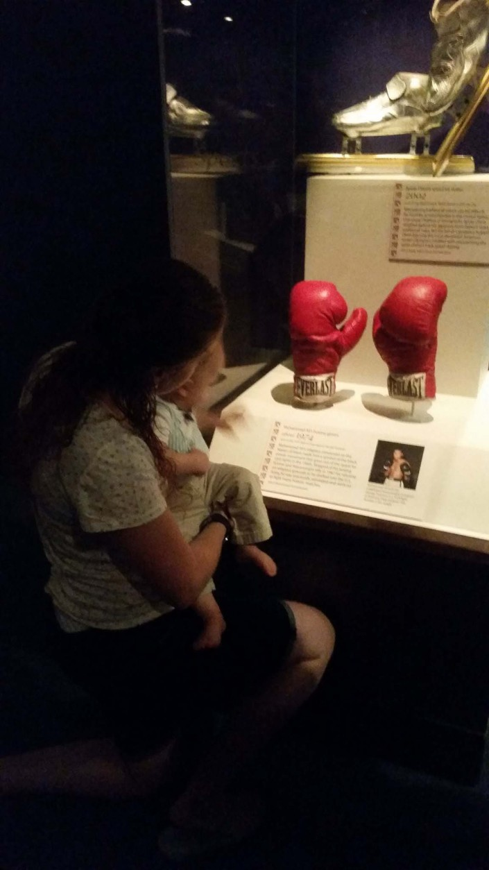 People look at Muhammad Ali's boxing gloves Saturday at the National Museum of American History in D.C. (WTOP/Allison Keyes)