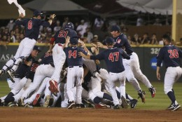 Arizona players celebrate after defeating Mississippi State 6-5 in 11 innings during an NCAA college baseball tournament super regional game in Starkville, Miss., Saturday, June 11, 2016. (AP Photo/Jim Lytle)