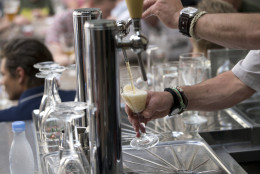 A worker pours a glass of beer for customers at the Halve Maan Brewery in Bruges, Belgium on Thursday, May 26, 2016. The brewery has recently created a beer pipeline which will ship beer straight from the brewery to the bottling plant, two kilometers away, through underground pipes running between the two sources. (AP Photo/Virginia Mayo)
