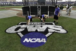 Groundskeepers paint the College World Series logo as Miami players practice at TD Ameritrade Park in Omaha, Neb., Friday, June 12, 2015. The NCAA College World Series baseball tournament starts on Saturday. (AP Photo/Mike Theiler)