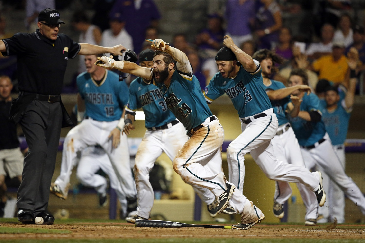 Coastal Carolina's Anthony Marks (29) reacts after sliding into home plate to score the winning run in the bottom of the ninth inning of an NCAA college baseball tournament super regional game against LSU in Baton Rouge, La., Sunday, June 12, 2016. Coastal Carolina won 4-3 to advance to the College World Series. (AP Photo/Gerald Herbert)