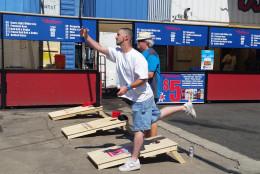 A participant in the DMV Cornhole Fest throws a bean bag Saturday in Southeast D.C. (WTOP/Allison Keyes)