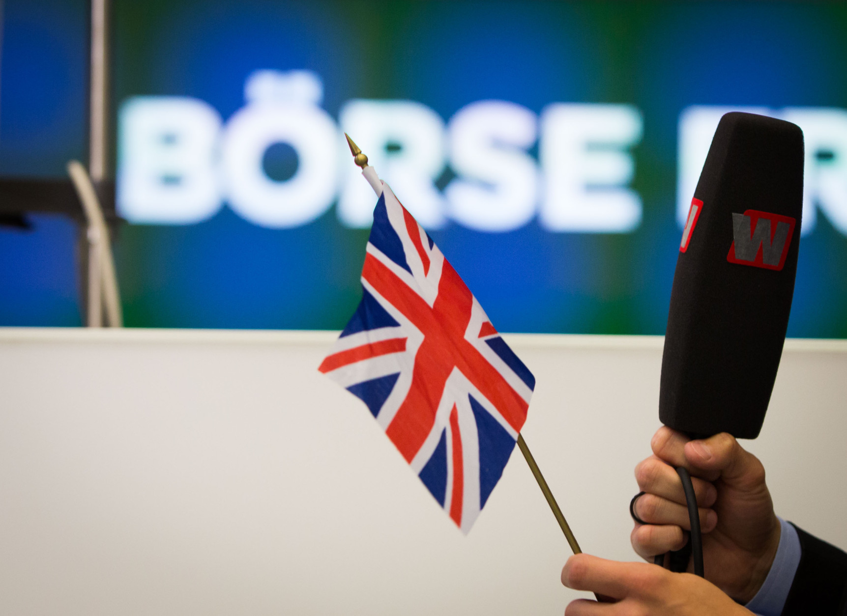 The anchor of a financial news channel holds a British flag as he reports from the trading floor of the Frankfurt, Germany, stock exchange Friday, June 24, 2016 after Britain voted to leave the EU. (Frank Rumpenhorst/dpa via AP)