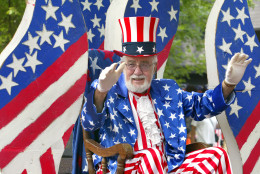 DES PLAINES, IL - JULY 3: A participant dressed in flag attire waves while riding on his float during the Fourth of July parade July 3, 2004 in Des Plaines, Illinois. America will celebrate its 228th birthday July 4, 2004. (Photo by Tim Boyle/Getty Images)