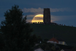 A full moon rises behind Glastonbury Tor as people gather to celebrate the summer solstice on June 20, 2016 in Somerset, England. Tonight's strawberry moon, a name given to the full moon in June by Native Americans because it marks the beginning of strawberry picking season, last occurred on the solstice on June 22, 1967 and it will not happen again on the summer solstice for another 46 years until June 21, 2062.  (Photo by Matt Cardy/Getty Images)