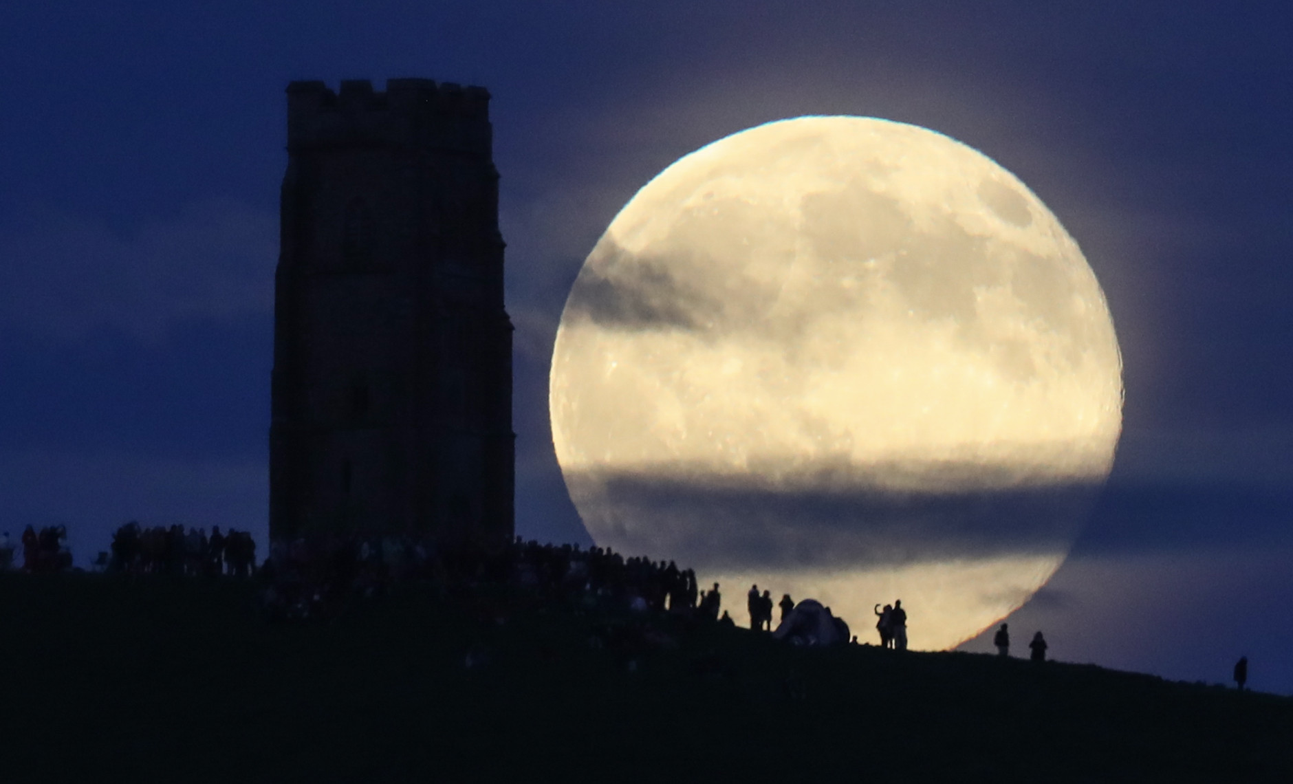 A full moon rises behind Glastonbury Tor as people gather to celebrate the summer solstice on June 20, 2016 in Somerset, England.  (Photo by Matt Cardy/Getty Images)