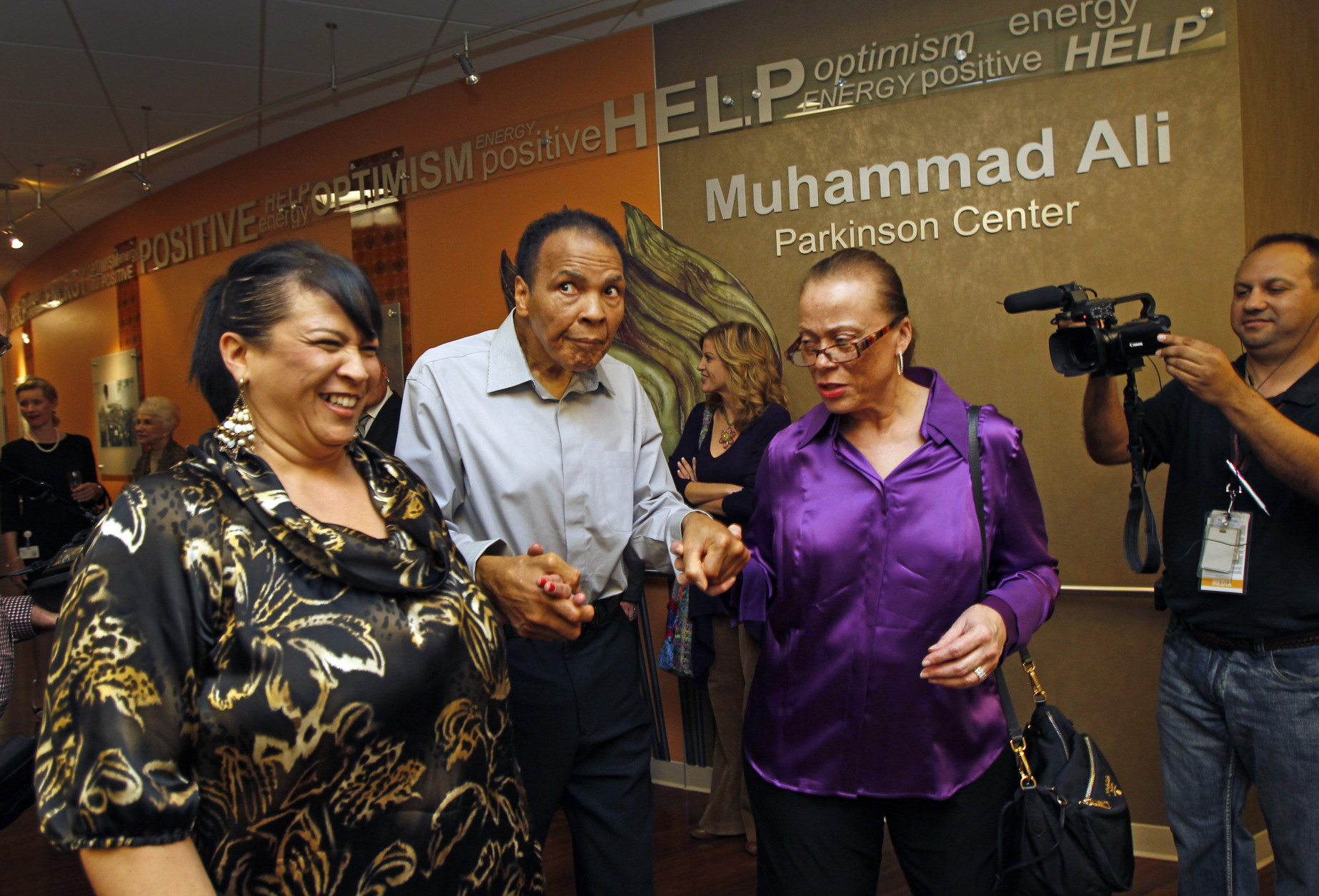 FILE - In this Feb. 22, 2012, file photo, Muhammad Ali, center, with the support of sister in-law Marilyn Williams, left, and wife Lonnie, walks through the Muhammad Ali Parkinson Center at Barrow Neurological Institute at St. Joseph's in Phoenix. Mohammed Ali is in the hospital with respiratory problems, and while officials haven't given details about his condition, the boxing great's health in general is complicated by advanced Parkinson's _ a degenerative disease he's lived with for three decades.  (AP Photo/The Arizona Republic, David Kadlubowski) MARICOPA COUNTY OUT; MAGS OUT; NO SALES