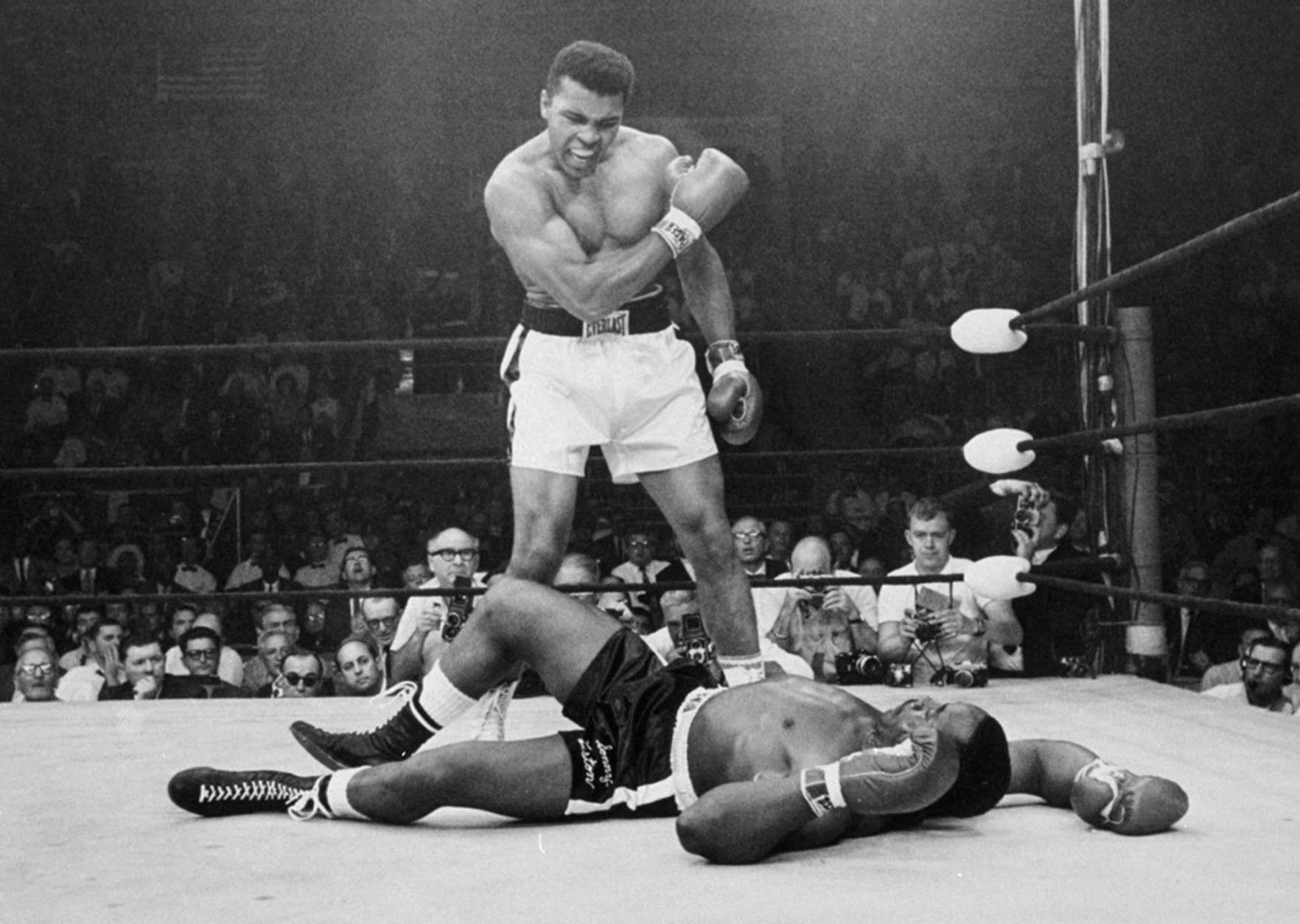 FILE - In this May 25, 1965, file photo, heavyweight champion Muhammad Ali, then known as Cassius Clay, stands over challenger Sonny Liston, shouting and gesturing shortly after dropping Liston with a short hard right to the jaw, in Lewiston, Maine. Ali, the magnificent heavyweight champion whose fast fists and irrepressible personality transcended sports and captivated the world, has died according to a statement released by his family Friday, June 3, 2016. He was 74.  (AP Photo/John Rooney, File)