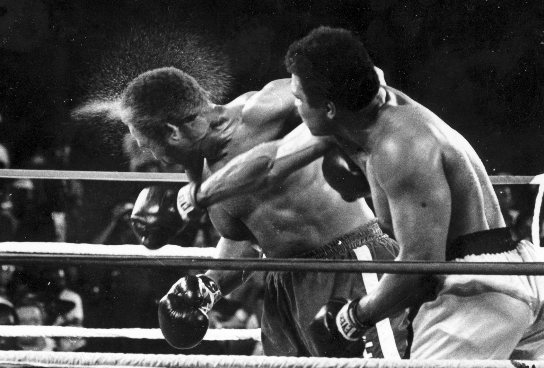 FILE - This is a Oct. 30, 1974,  file photo showing George Foreman taking a right to the head from challenger Muhammad Ali in the seventh round in the match dubbed Rumble in the Jungle in Kinshasa, Zaire. Ali, the magnificent heavyweight champion whose fast fists and irrepressible personality transcended sports and captivated the world, has died according to a statement released by his family Friday, June 3, 2016. He was 74. (AP Photo/Ed Kolenovsky, File)