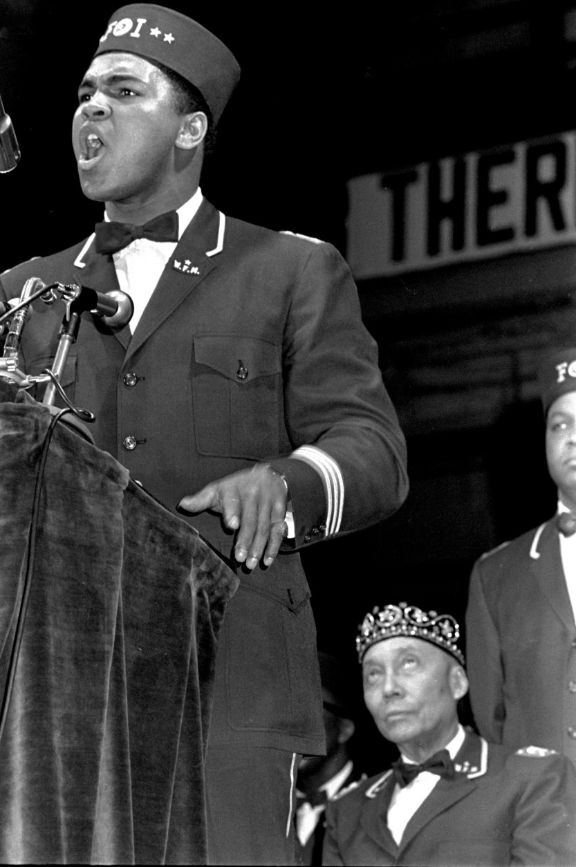 FILE - In this Feb. 25, 1968, file photo, former heavyweight boxing champion Muhammad Ali speaks at a Black Muslim convention in Chicago. Seated behind Ali is Elijah Muhammad, leader of the Nation of Islam. Ali, the magnificent heavyweight champion whose fast fists and irrepressible personality transcended sports and captivated the world, has died according to a statement released by his family Friday, June 3, 2016. He was 74. (AP Photo/file)