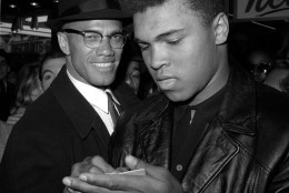 FILE - In this March 1, 1964, file photo, world heavyweight boxing champion, Muhammad Ali, right, is shown with Black Muslim Leader, Malcolm X, outside the Trans-Lux Newsreel Theater  in New York City, after watching a screening of films on Ali's title fight with Sonny Liston in Miami Beach. Ali, the magnificent heavyweight champion whose fast fists and irrepressible personality transcended sports and captivated the world, has died according to a statement released by his family Friday, June 3, 2016. He was 74. (AP Photo)