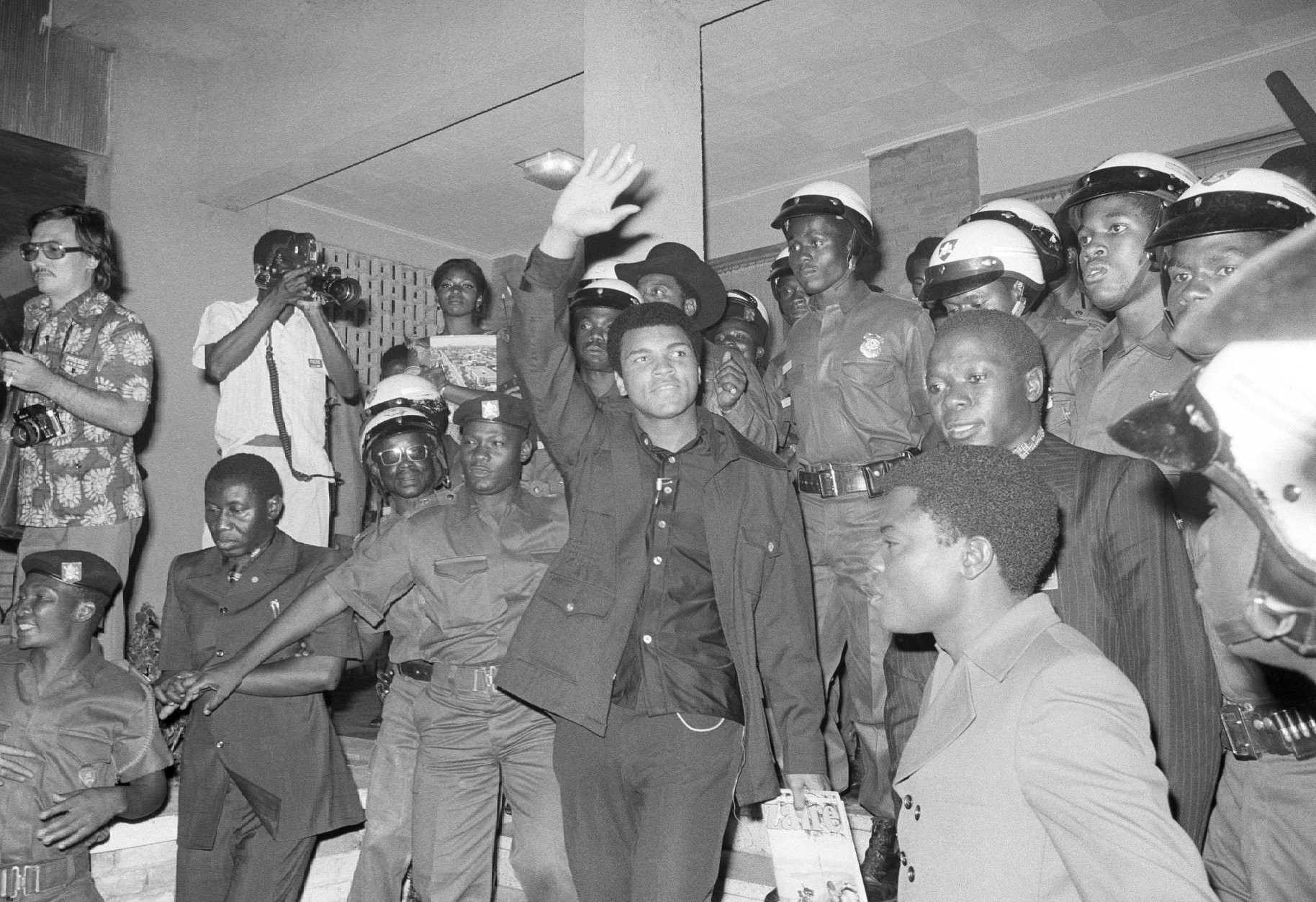 FILE - In this Sept. 11, 1974, file photo, heavyweight title challenger Muhammad Ali, surrounded by Zaire soldiers, waves to crowd upon his arrival in Kinshasha, Zaire. Ali is in Zaire for a fight against George Foreman. Ali, the magnificent heavyweight champion whose fast fists and irrepressible personality transcended sports and captivated the world, has died according to a statement released by his family Friday, June 3, 2016. He was 74. (AP Photo/Horst Faas, File)