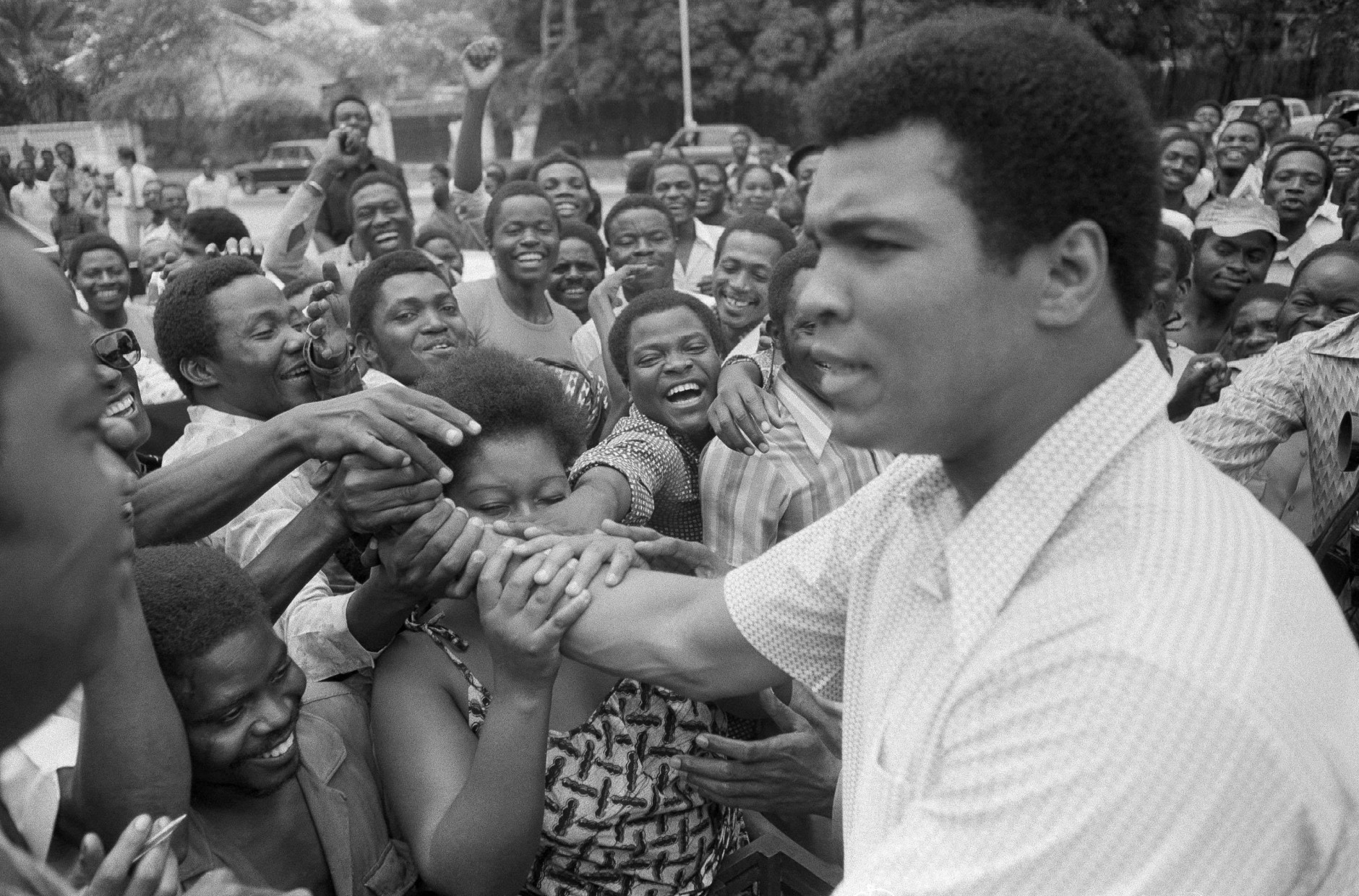FILE - In this Sept. 17, 1974, file photo, Muhammad Ali is greeted in downtown Kinshasa, Zaire. Ali is in Zaire to fight George Foreman. Ali, the magnificent heavyweight champion whose fast fists and irrepressible personality transcended sports and captivated the world, has died according to a statement released by his family Friday, June 3, 2016. He was 74. (AP Photo)