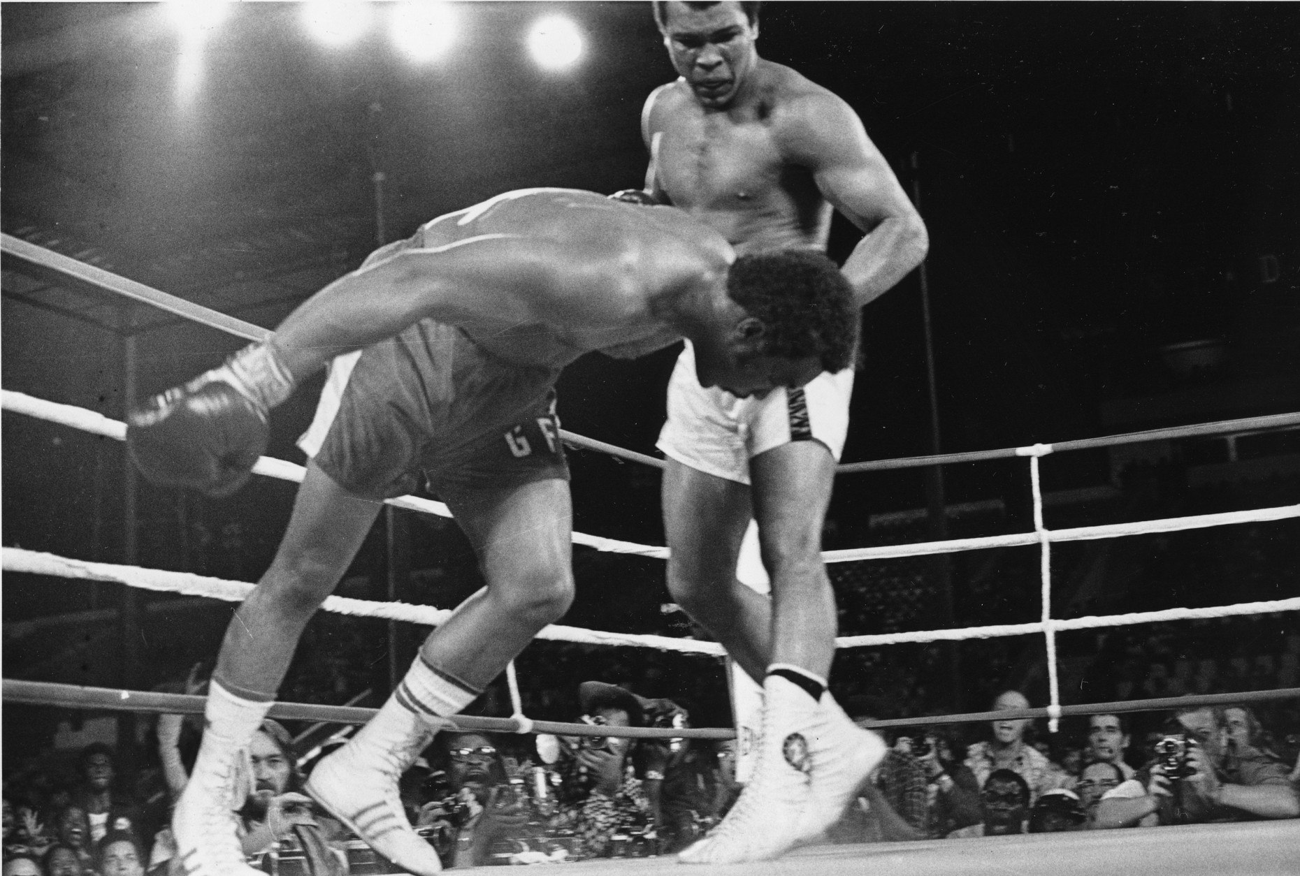 FILE - In this Oct. 30, 1974, file photo, challenger Muhammad Ali watches as defending world champion George Foreman goes down to the canvas in the eighth round of their WBA/WBC championship match in Kinshasa, Zaire. Ali, the magnificent heavyweight champion whose fast fists and irrepressible personality transcended sports and captivated the world, has died according to a statement released by his family Friday, June 3, 2016. He was 74. (AP Photo/File)